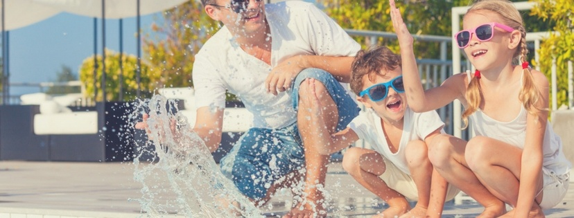 father and children happy at swimming pool