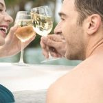 happy couple relax and drink at hot tub