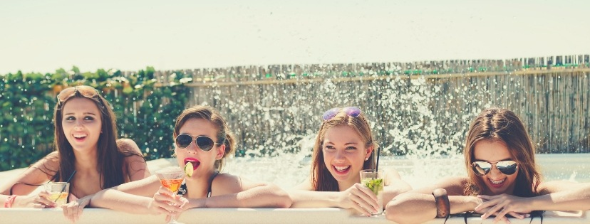 fun girls drink juice at the hot tub